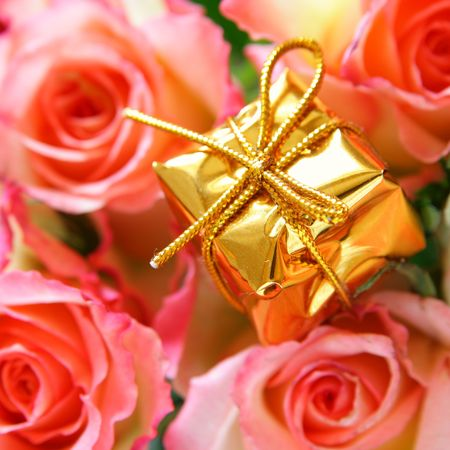 Gold box with gift and rosebuds in the background out of focus photo