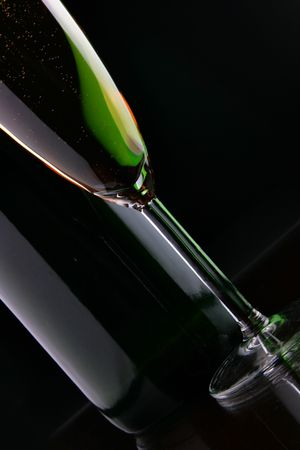 Glass and bottle of champagne close-up over black background Stock Photo - 3899249