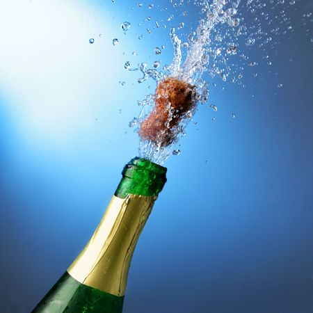 Bottle of champagne with splashes over blue background photo
