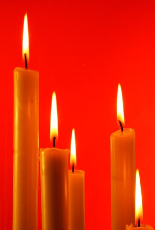 Five burning candles over light red background   photo