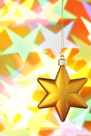 Gold Christmas star close-up over colorful background photo