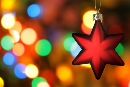 bedeck: Red Christmas star close-up over colorful background Stock Photo