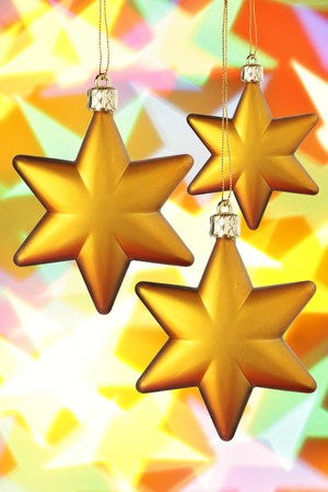 Gold Christmas stars close-up over colorful background photo
