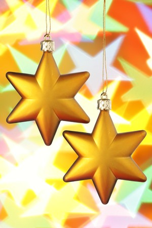 bedeck: Gold Christmas stars close-up over colorful background