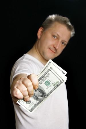 subornation: Man offering money over black background. Focus on the money!
