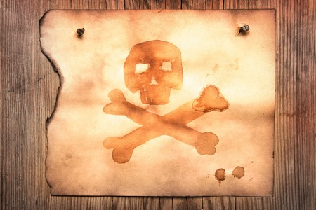 Old paper with jolly roger attached to wooden wall Stock Photo - 4137068