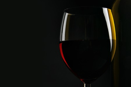 taster: Still-life with glass of red wine over black background