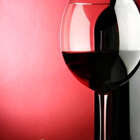Glass and bottle of wine over red background Stock Photo - 4165941
