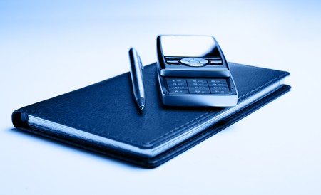 scheming: Cellular phone and pen on leather organizer toned in blue color Stock Photo