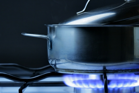 gas cooker: Crock on the gas stove over black background Stock Photo