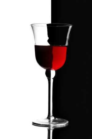 bar ware: Glass of red wine over contrast black and white background