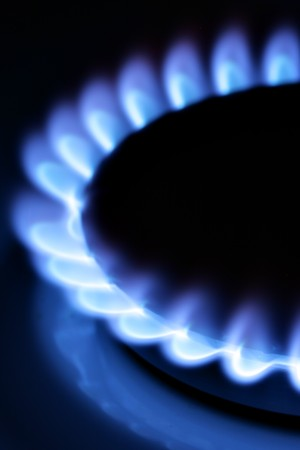Blue gas flame on hob close up in the dark photo