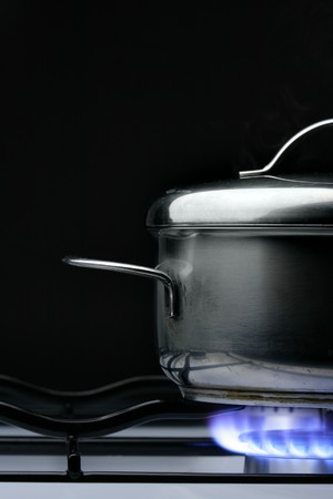 Crock on the gas stove over black background photo