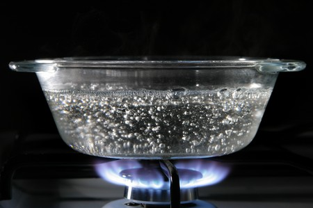 Glass saucepan on the gas stove close-up photo