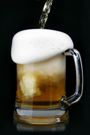 scum: Pouring beer into mug over black background
