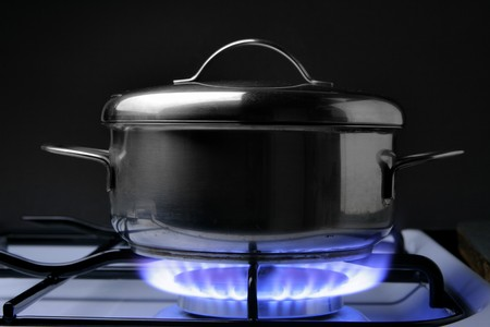 crock: Crock on the gas stove over black background Stock Photo