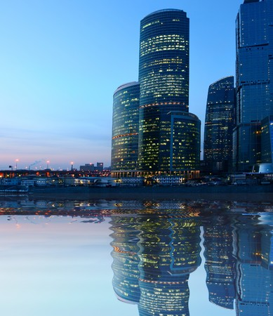 Modern skyscrapers at night on river bank photo