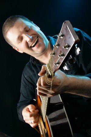 Man playing acoustic guitar at rock concert photo