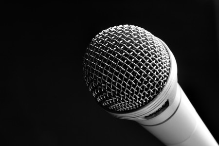 up close image: Microphone close up over a black background