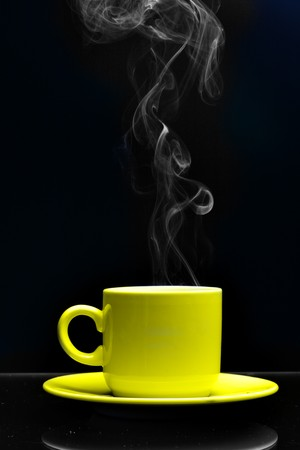 Cup of hot drink close-up with steam over black background photo