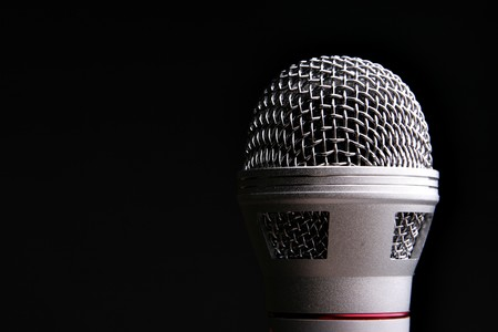 Microphone close up over a black background photo