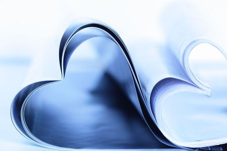 periodical: Two magazines folded to heart shape on table