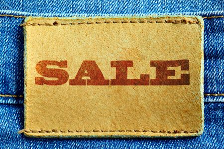 Blue jeans and leather label with word Sale photo
