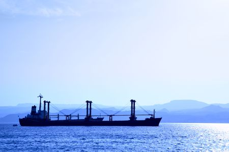 Cargo ship at the harbour. View from Jordan shore to Israel Stock Photo - 4949195