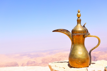Arabic coffee pot on the stone and Jordan's mountains in the background 스톡 콘텐츠