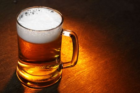taverns: Mug of beer close up on wooden table Stock Photo