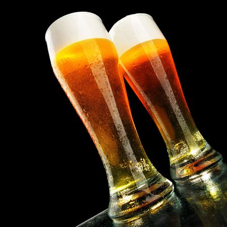 casal: Two glasses of beer with froth over black background