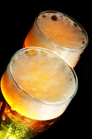 Two glasses of beer with froth over black background photo