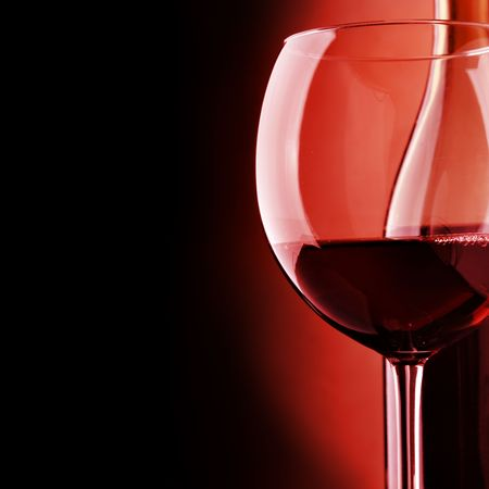Glass and bottle of wine over black background photo