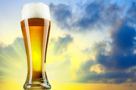 Beer glass with froth and sundown in the background