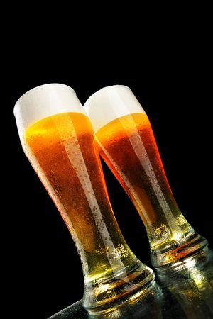 Two glasses of beer with froth over black background Stock Photo