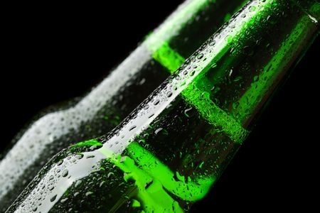 Close up of two beer bottles over black background photo