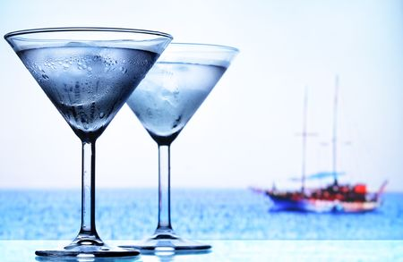 bar ware: Two cocktail glasses and sea in the background