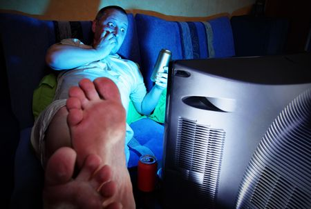 thriller: Man watching thriller and drinking beer Stock Photo