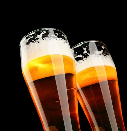 unbottled: Two glasses of beer with froth over black background