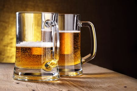 beerhouse: Two beer mugs close-up on wooden table Stock Photo