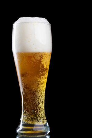 backlit: Vaso de cerveza con espuma sobre fondo negro