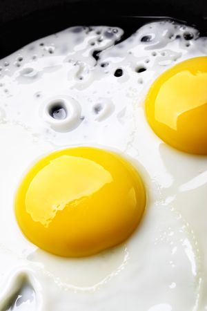 cook griddle: Two fried eggs on pan close up Stock Photo
