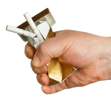 Mans hand crushing cigarette box isolated over white background photo