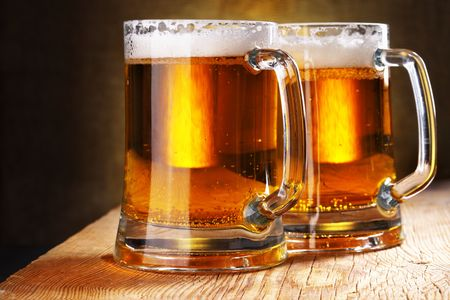 Two beer mugs close-up on wooden table Stock Photo - 5717341