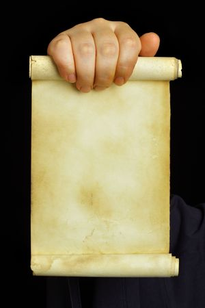 vow: Hand holding old manuscript over black background
