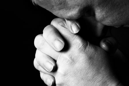 arrepentimiento: Hombre orar por algo sobre el fondo negro