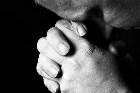 Man pray for something over the black background photo