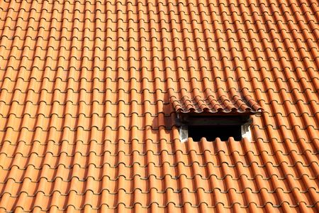 Old red tiled roof with small window Stock Photo - 5717387