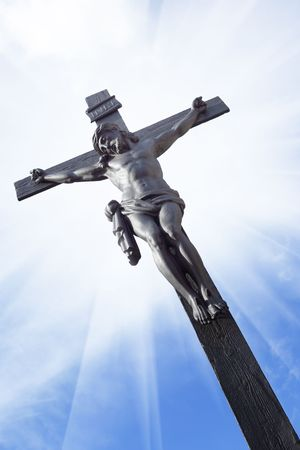 trustful: Jesus on the cross against a blue sky with glare  Stock Photo