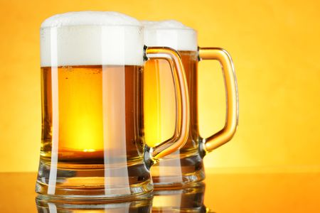 unbottled: Beer mugs with froth over yellow background